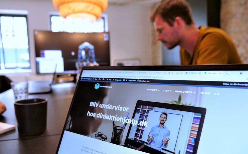 computerskærm i forgrunden og mand i baggrunden